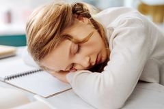 Cute child sleeping over her books. Tired. Pretty sweet fair-haired little schoolgirl sleeping over her books while sitting at the table and doing homework Royalty Free Stock Images