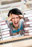 Tired pretty woman surrounded with books. Tired pretty woman with headache sitting at the desk surrounded with piles of books Royalty Free Stock Photo