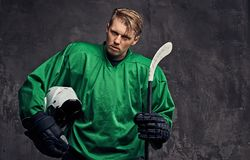 Free Tired Professional Hockey Player In A Green Sportswear Holds A Hockey Stick And Protective Helmet On A Gray Background. Royalty Free Stock Photography - 119350817