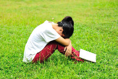 Tired of reading. Young woman tired of reading on green grass Royalty Free Stock Photography