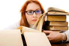 Tired red-haired girl in glasses with books. Royalty Free Stock Photo