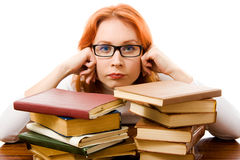 Tired red-haired girl in glasses with books. Stock Photo