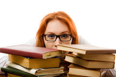 Tired red-haired girl in glasses with books. Stock Image