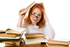 Tired red-haired girl in glasses with books Stock Image