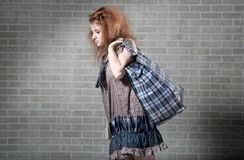 Tired redhaired woman with shopping bag. Royalty Free Stock Images