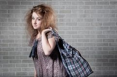 Tired redhaired woman with shopping bag. Royalty Free Stock Image