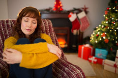 Tired redhead sitting on the armchair at christmas Royalty Free Stock Images