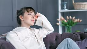 Tired relaxed young woman stretching raising hands sitting on couch in cozy sweater at home interior stock video footage