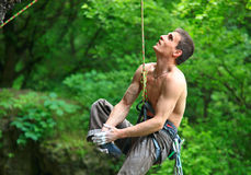 Tired rock climber hanging on rope. Tired rock climber hanging on the rope and looking up after falling off from the route Stock Images