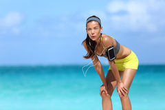 Tired runner girl breathing taking a run break. Tired runner breathing taking a run break on beach with ocean background. Asian chinese athlete woman resting stock photos