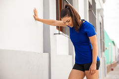 Tired runner leaning on a wall. Pretty brunette in sporty outfit taking a break and leaning against a wall to get some air after her workout Royalty Free Stock Images