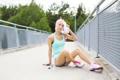 Tired runner sitting on the ground and having a break Stock Photo