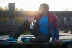 Tired runner sitting, relaxing and listening to music phone on a wooden pier, sport Stock Photography