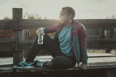 Tired runner sitting, relaxing and listening to music phone on a wooden pier, sport. Stock Image