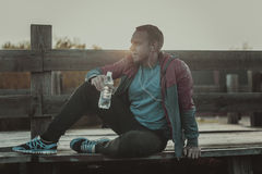 Tired runner sitting, relaxing and listening to music phone on a wooden pier, sport. Royalty Free Stock Images