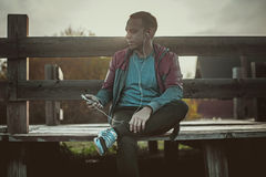 Tired runner sitting, relaxing and listening to music phone on a wooden pier, sport Royalty Free Stock Images
