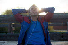 Tired runner sitting, relaxing and listening to music  your phone, eyes closed on a wooden pier, sport. Stock Photos