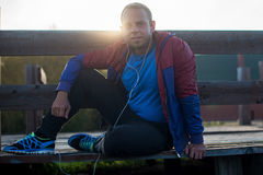 Tired runner sitting, relaxing and listening to music your phone on a wooden pier, sport. Stock Photos