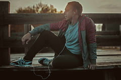 Tired runner sitting, relaxing and listening to music your phone on a wooden pier, sport. Royalty Free Stock Photography