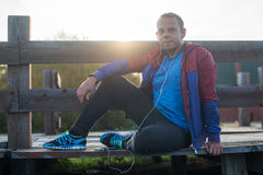 Tired runner sitting, relaxing and listening to music your phone on a wooden pier, sport. Stock Images