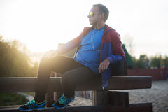 Tired runner sitting, relaxing and listening to music your phone on a wooden pier, sport Stock Photography