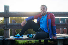 Tired runner sitting, relaxing and listening to music your phone on a wooden pier, sport. Stock Photo