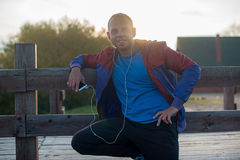 Tired runner standing, relaxing and listening to music your phone on a wooden pier, sport Stock Photography