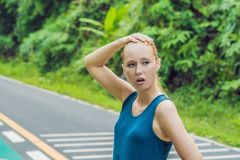 Tired runner sweating after running hard in countryside road. Exhausted sweaty woman after marathon training on hot royalty free stock photos