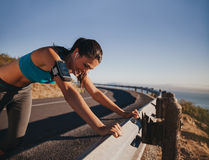 Tired runner taking a break leaning guardrail. Tired runner taking a break leaning on country road guardrail. Fit young woman athlete training outdoors Royalty Free Stock Images