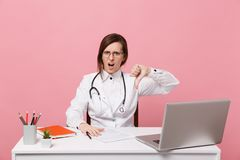 Tired sad female doctor sits at desk work on computer with medical document in hospital isolated on pastel pink wall royalty free stock photo