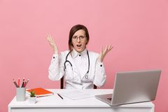 Tired sad female doctor sits at desk work on computer with medical document in hospital  on pastel pink wall