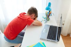 Tired or sad student boy with laptop at home. Education, cyberbullying and people concept - tired or sad student boy with laptop computer lying on desk at home Royalty Free Stock Photo