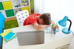 Tired or sad student boy with laptop at home. Education, cyberbullying and people concept - tired or sad student boy with laptop computer lying on desk at home Stock Photo
