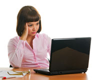 Tired and sad view in office. Girl in the office sits at a table with a laptop with a tired and sad view Stock Image