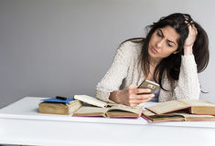 Tired  sad  woman  studying for exams with phone in the hand Royalty Free Stock Image