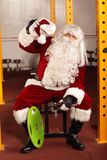 Tired Santa Claus- break in training before Christmas in gym. Santa Claus physical condition training before Christams time in gym royalty free stock photos