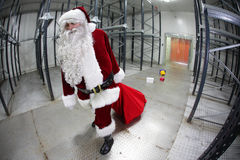 Tired Santa Claus loosing gifts from red sack Royalty Free Stock Photo