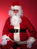 Tired santa claus is resting by sitting on a chair Royalty Free Stock Photography
