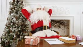 Tired Santa Claus waking up from a nap to continue preparing presents. Professional shot on Lumix GH4 in 4K resolution. You can use it e.g. in your commercial Royalty Free Stock Image