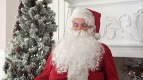 Tired Santa Claus waking up from a nap to continue preparing Xmas presents.  Stock Images