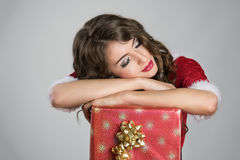 Tired Santa helper girl sleeping comfortable on big red box with golden ribbon Stock Photography
