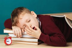 Tired school boy asleep on books. little student sleeping on tex. Tbooks. Child in school uniform lies on the table with big pile of books against blue wall Stock Photos