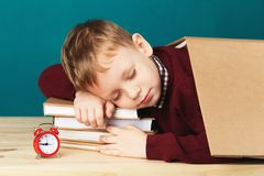 Tired school boy asleep on books. little student sleeping on tex. Tbooks. Child in school uniform lies on the table with big pile of books against blue wall Stock Photography