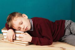Tired school boy asleep on books. little student sleeping on tex. Tbooks. Child in school uniform lies on the table with big pile of books against blue wall Royalty Free Stock Photography