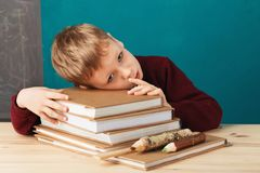 Tired school boy asleep on books. little student sleeping on tex. Tbooks. Child in school uniform lies on the table with big pile of books against blue wall Stock Photo