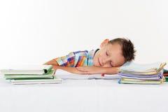 Tired school boy is sleeping on desk Stock Photography