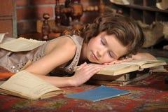 Girl fell asleep among the books Royalty Free Stock Image