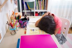 Tired school girl doing homework Stock Photos
