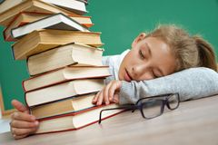 Tired school girl fell asleep on the table among books. Photo of little girl in school. Education concept Royalty Free Stock Photos