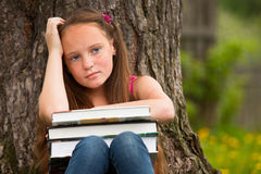 Tired school girl in the park Stock Photos